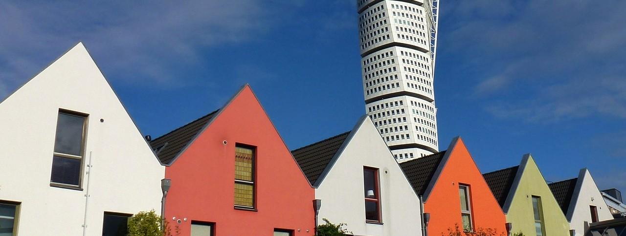 """farbige Häuse in Västra Hamnen/Malmö, im Hintergrund das Hochhaus """"Turning Torso"""""""